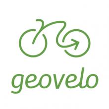 Lettres stylisées vertes sur fond blanc, surmontées du dessin d'un vélo dont le tracé s'achève par une flèche.