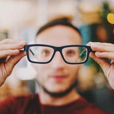 Photo d'un personne regardant l'objectif au travers d'une paire de lunettes tenue à distance.