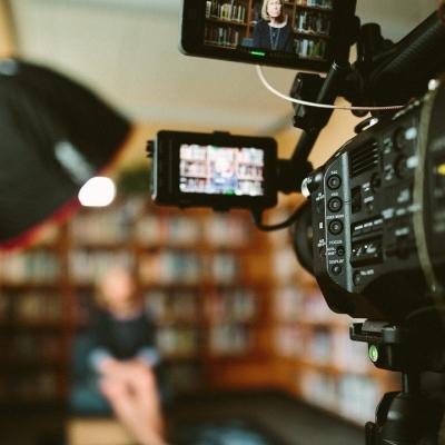 Une caméra au premier plan filmant une personne au second.