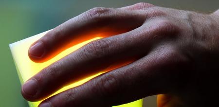 Une main posée sur un carré luminescent.