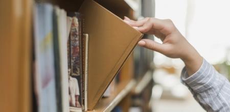 main prenant un livre sur une étagère