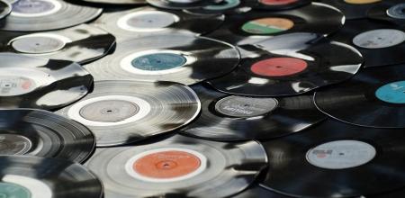 Disques vinyles sans pochettes agencés au sol.