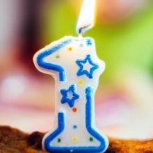 Gros plan d'une bougie d'anniversaire (chiffre 1) allumée sur un gâteua d'anniversaire