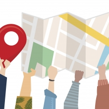 Illustration de mains portant un plan et une punaise de localisation.