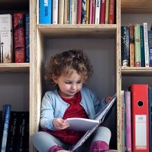 Une petite fille lit un livre assise dans le bas d'une bibliothèque en bois.