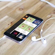smartphone sur une table avec ses écouteurs. Sur l'écran on voit la page d'accueil d'1DTouch
