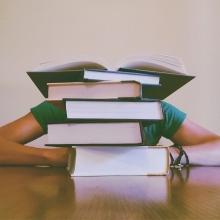 Un étudiant dormant sur son bureau dissimulé derrière une pile de livres.