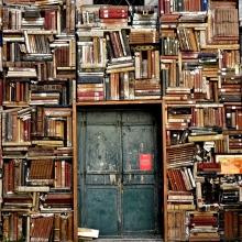 Mur vu de face constitué entièrement de manuscrits. Au centre, une porte en bois.