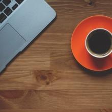 Vue de haut d'une tasse à café de couleur orange placée aux côtés d'un ordinateur portable.