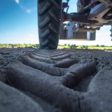 Marques de roues de tracteur sur une terre meuble.