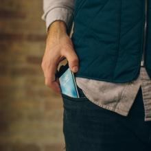 Homme sortant un téléphone portable de sa poche.