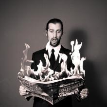 homme lisant un journal en feu