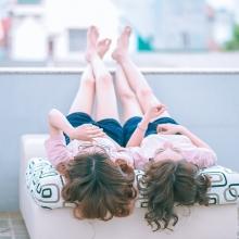 Deux femmes côte à côte sont allongées sur un lit et nous tournent le dos. Leurs pieds sont posés sur un muret
