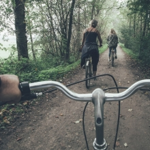 Vue subjective d'une personne roulant à vélo sur un chemin forestier. Deux autres vélos précédent le cycliste.